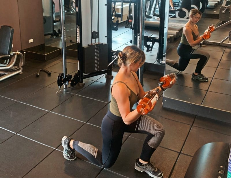 Woman in gym doing lunge holding bottles of AIX Provence rose wine as weights