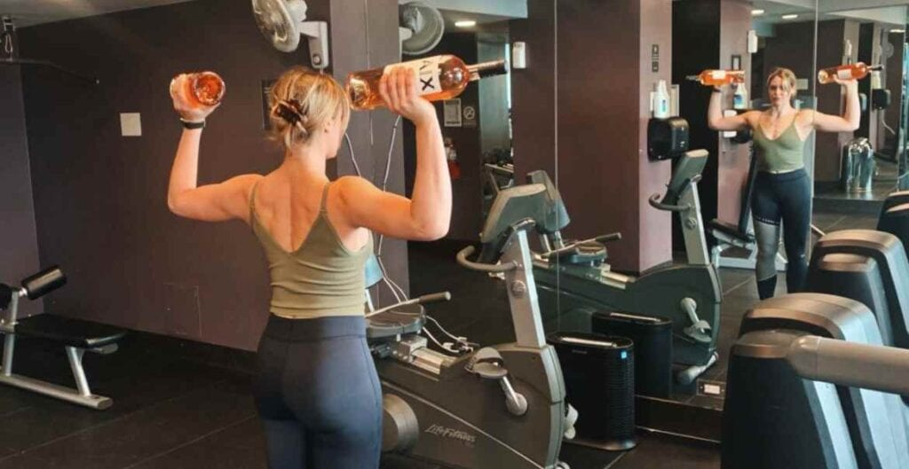 Woman lifting AIX Provence France French rose magnum wine bottles in a gym in front of mirror