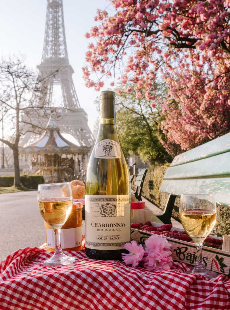 Bottle of Chardonnay on table in front of Eiffel Tower in Paris, France with two wine glasses
