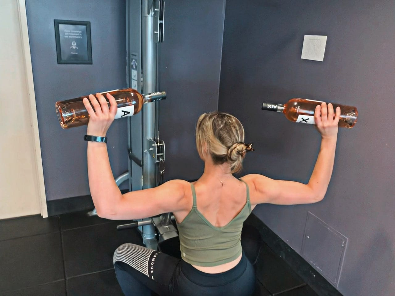 Woman in gym lifting two bottles of AIX Provence Rose as dumbbell weights