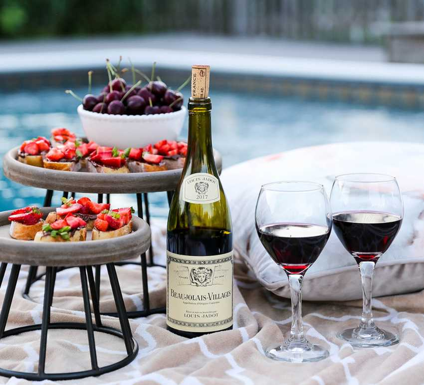 Red French wine by the pool with cherries and bruschetta
