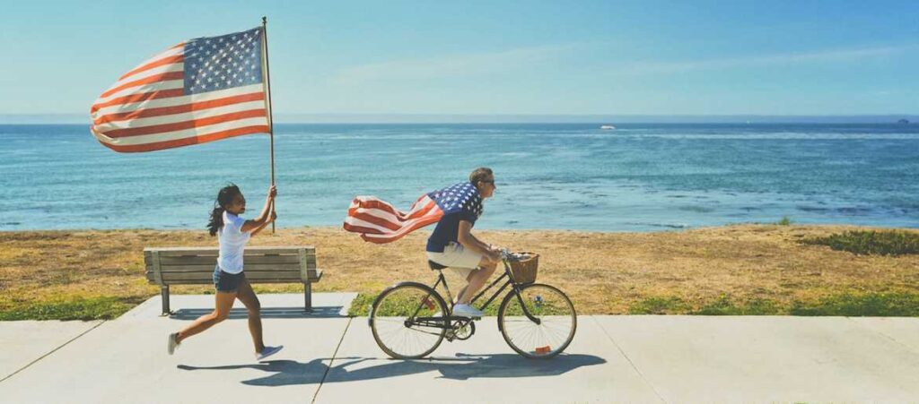 Running and biking with American flags by the ocean for Fourth of July