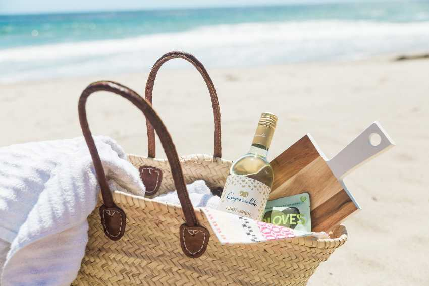 Pinot Grigio wine in a basket on the beach