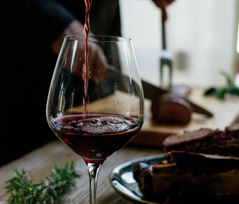 Red wine poured in glass at table