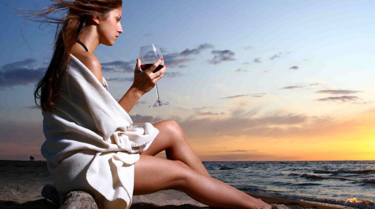 a beautyful young woman drinking wine on the beach