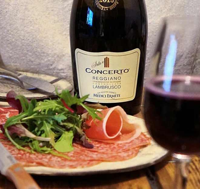 Bottle of Medici Ermete Concerto Lambrusco dry red wine from Emilia-Romagna next to Italian cured meats