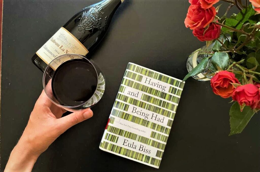 Book and wine with roses on table
