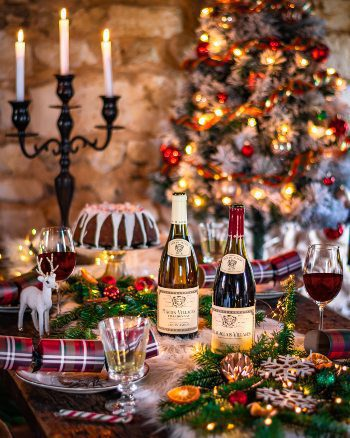 Louis Jadot wine at Christmas table with candles, tree, lights