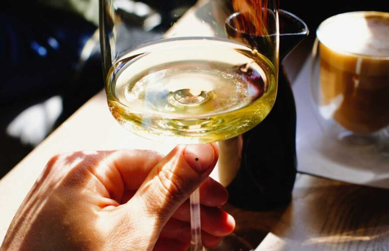 Hand holding glass of white wine