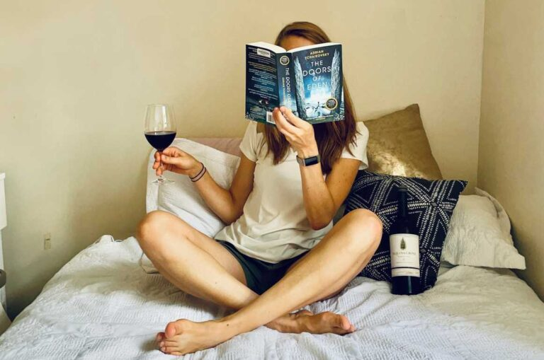 Reading book on bed with wine